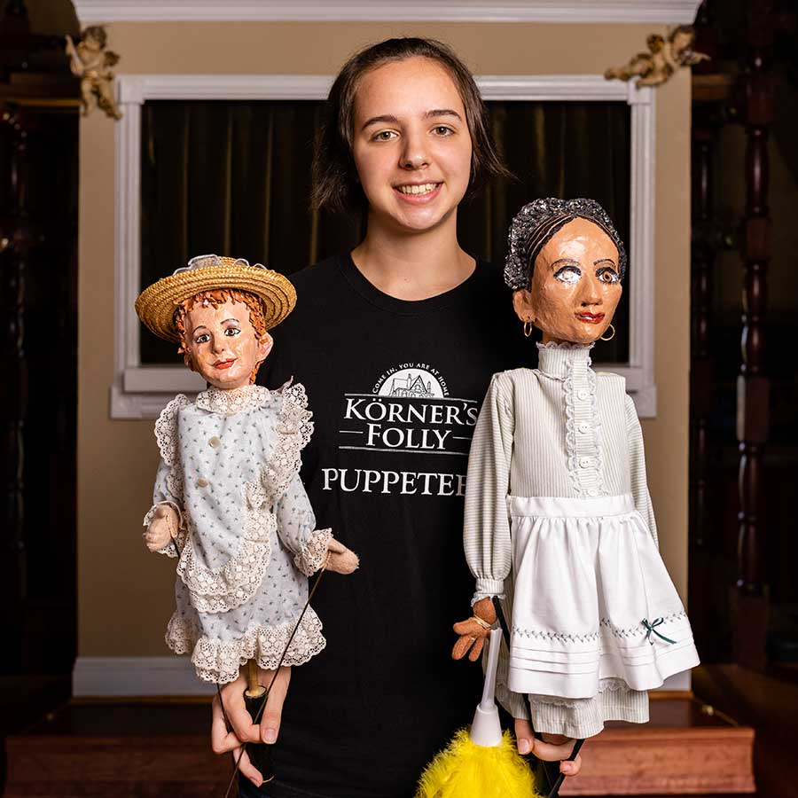 Lindsey Hart in black shirt holding two puppets.