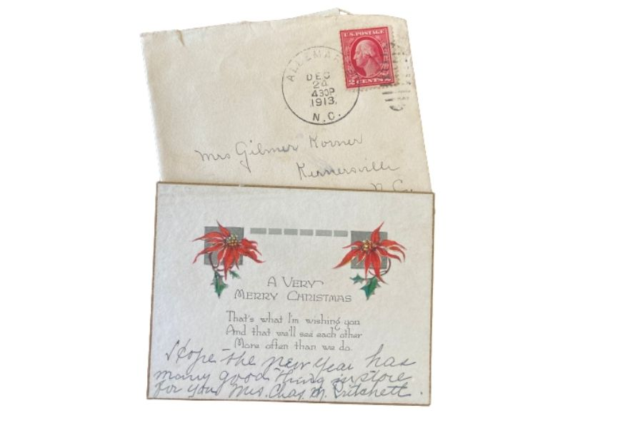 A square envelope and Christmas card featuring red poinsettias.